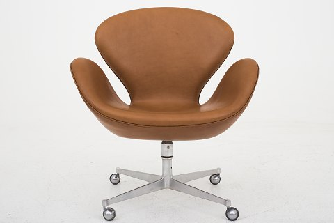 "Arne Jacobsen / Fritz Hansen AJ 3324 - Reupholstered ""The Swan"" in KLASSIK Cognac leather, wheels and tilt function. Old base Availability: 6-8 weeks We can offer upholstery of the Swan in fabric or leather of your choice. Please contact us for more information."