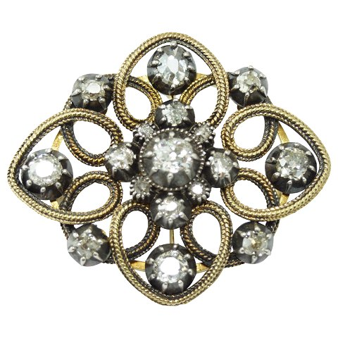 A diamond brooch mounted in 14k gold and white gold