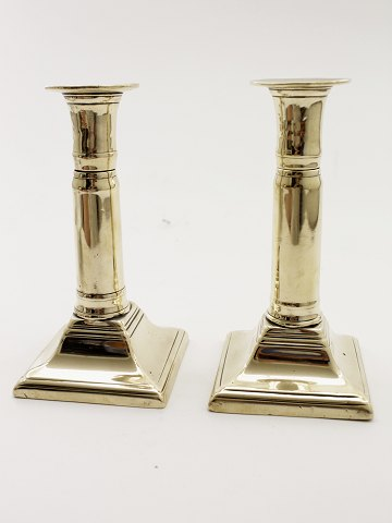 A pair of brass empire telescope candlesticks
