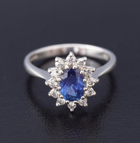 A ring set with a sapphire and wreathed with diamonds, in total 0,36 ct. mounted in 18 kt. white gold