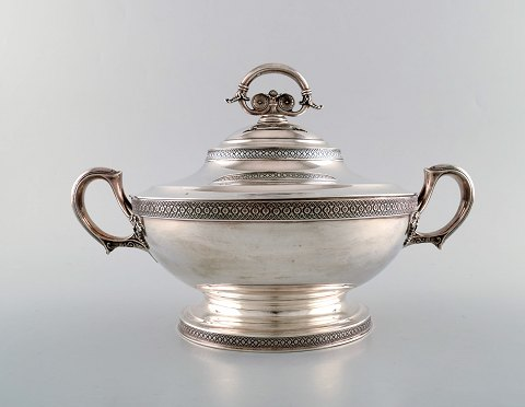 Tiffany & Company (New York). Stylish sterling silver tureen with stylized ornament. Curved and oval bowl on raised oval foot. 1870's